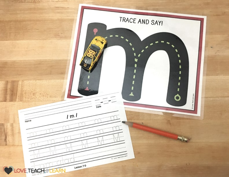 Lowercase letter M tracing mat and handwriting page for practicing penmanship.